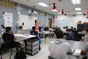 Engineering instructor Laura Doyle outlines pinhole camera project in new Innovation Classroom at Westfield High School.  The new space includes a digital presentation podium, LED lighting, laptops with computer aided design (CAD) capabilities, motorized window shades, retractable ceiling mounted power cords, and furniture on wheels.