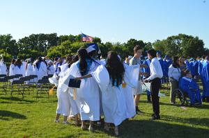 Group of girls dressed in their white graduation gowns run toward one another for a group hug