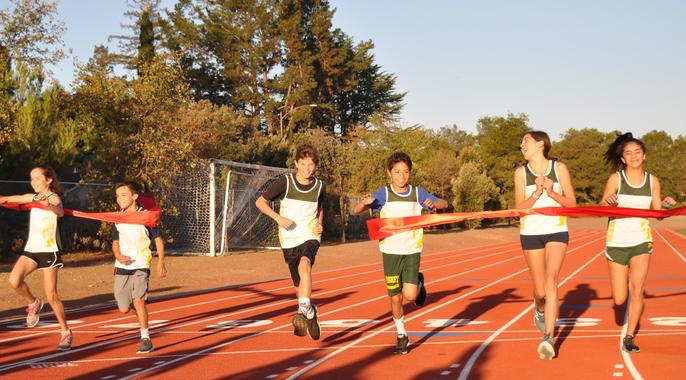 Student Runners Breaking Through Ribbon on Track