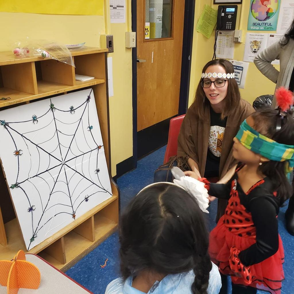 Ms. Viera dressed as a flower child watching a little girl dressed as a lady playing pin the spider to the web