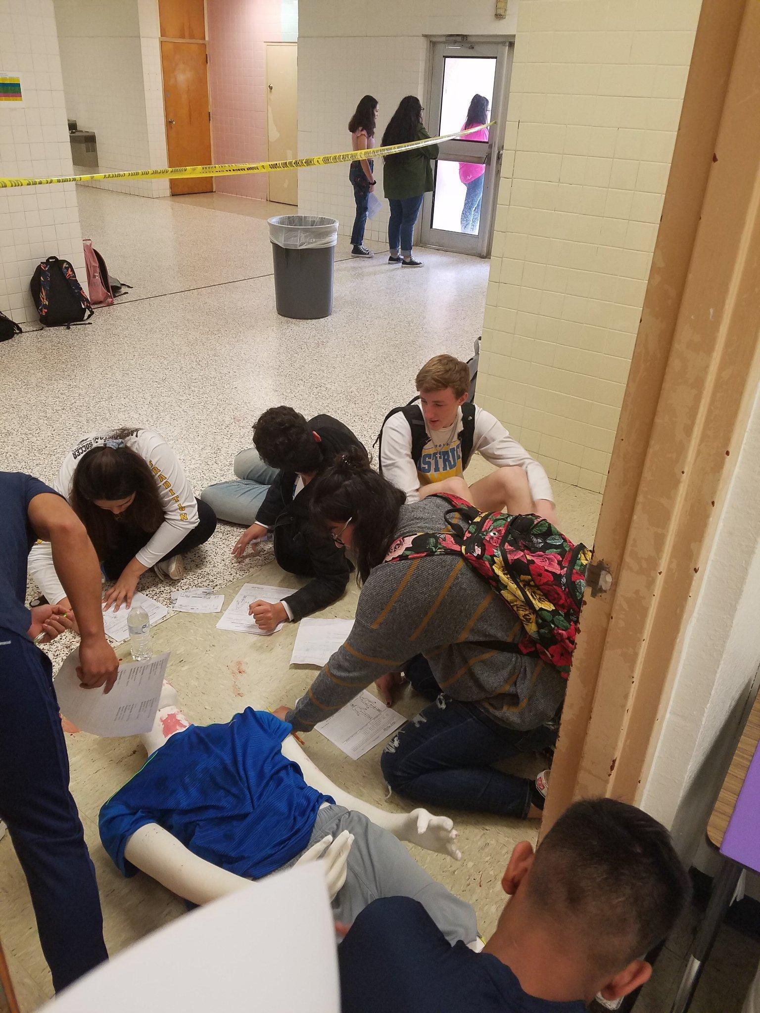 students sitting in a circle on the floor working on a project