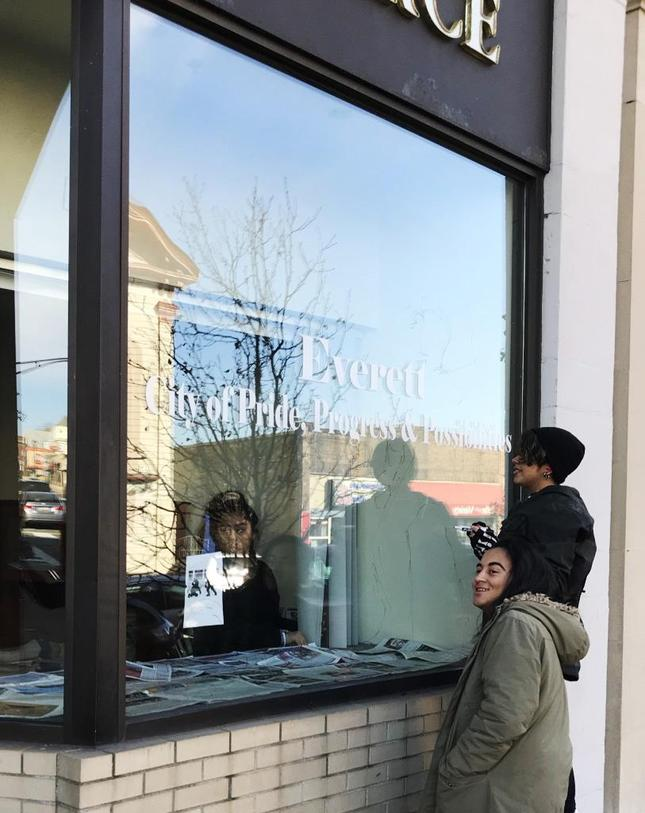 Two students look through the window of an Everett Square business