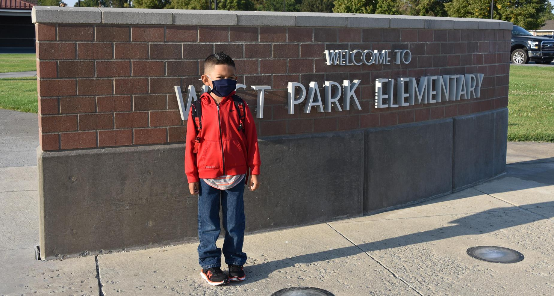 Student standing in front of West Park's sign.