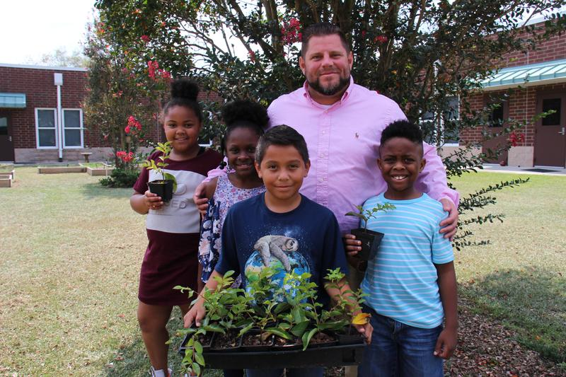 Pictured from left to right are Caidence Garvin, Olivia Anderson, Leonardo Gonzales, and Grayson Grant, all third grade students at B-L Elementary School. They are seen with Principal Matt Velasquez holding some of the Carolina Crepe Myrtle seedlings that were gifted to students in their grade level through MCEC's TreeMendUs program.