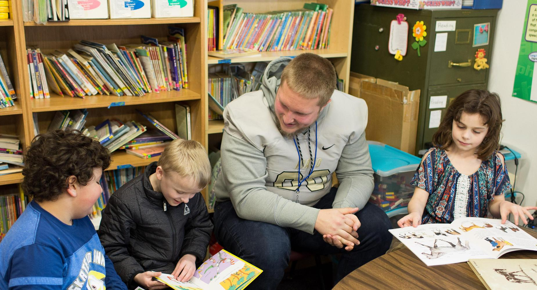 Vandal Football player reading to 2nd Graders