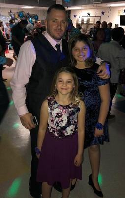Father and daughters all dressed up and ready for dance