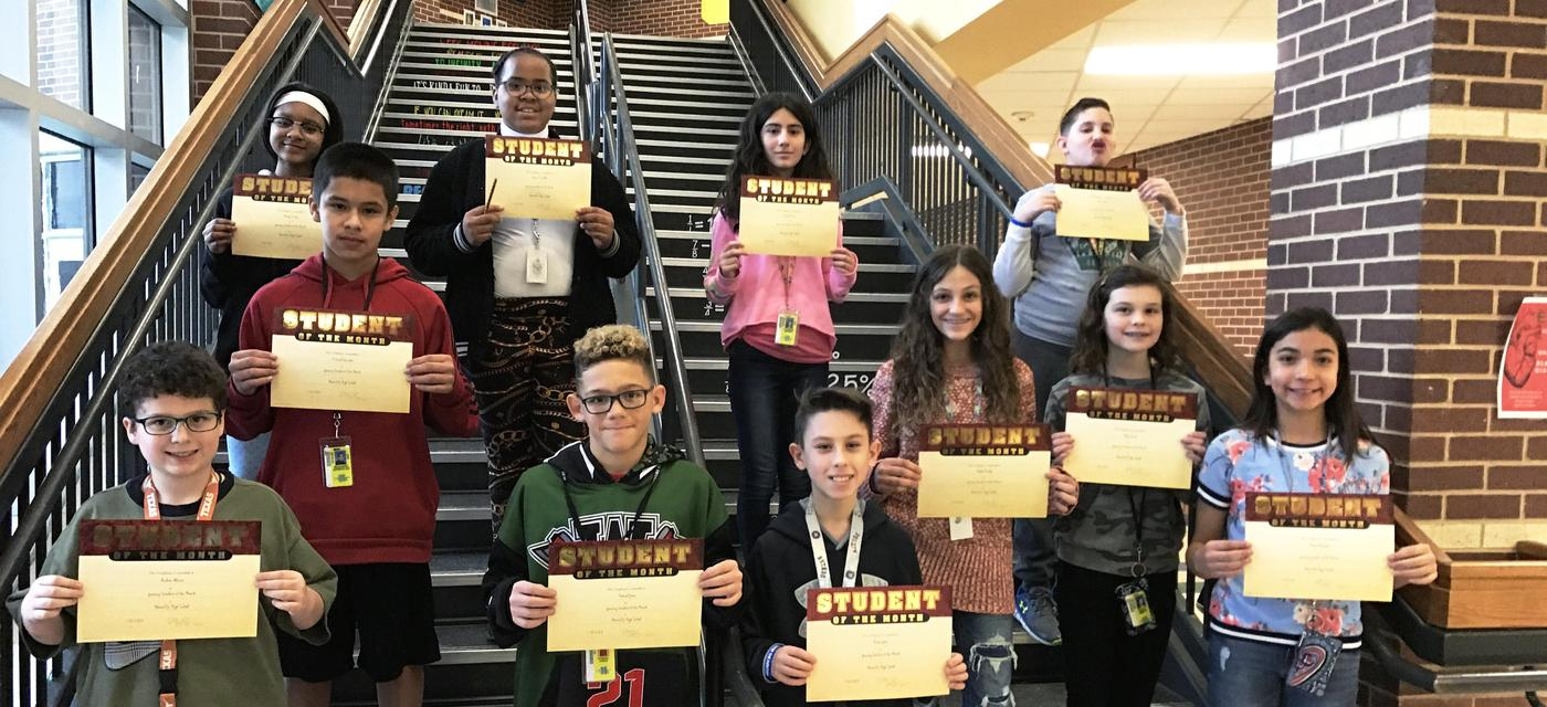 group of 11 students pose on steps with student of the month certificates