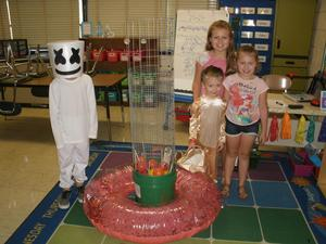 Children in their costumes are standing next to a game, ready to play.