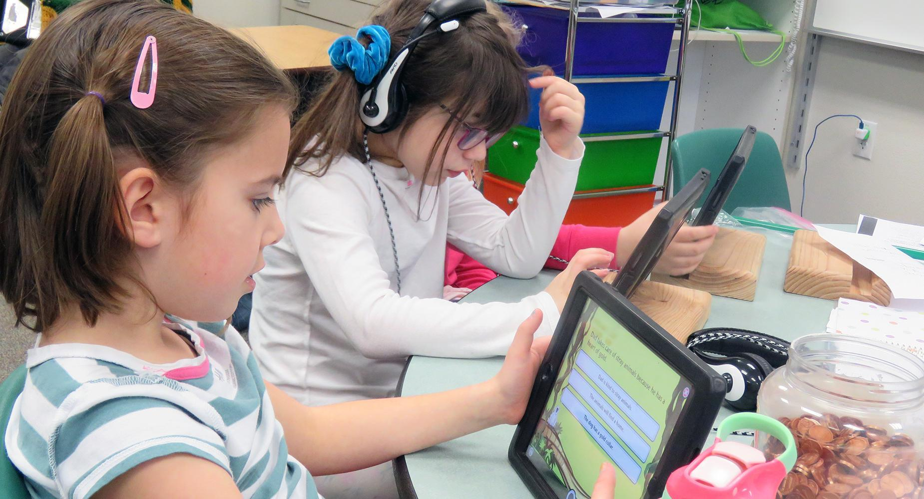 Two girls work on the iPads at their desk.