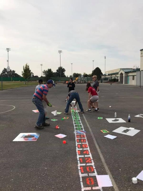 Volunteers help paint the number line at Snake River Elementary.