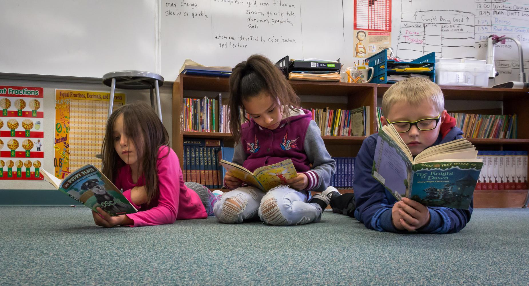 Three children lay on the carpet to read books