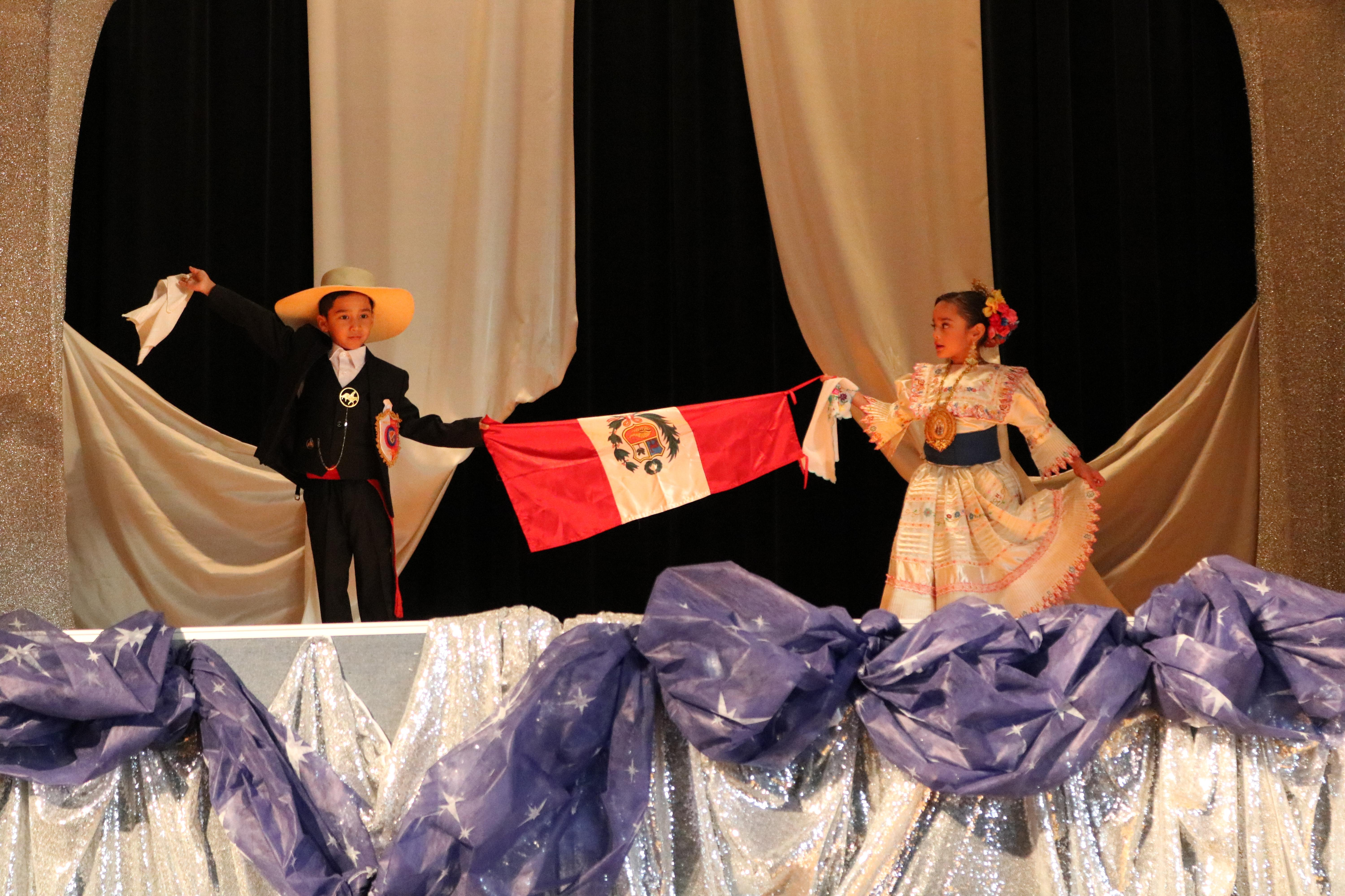 two children dressed in the Peruvian cultural dress holding the Peruvian flag