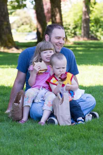Father and two children eating in a park