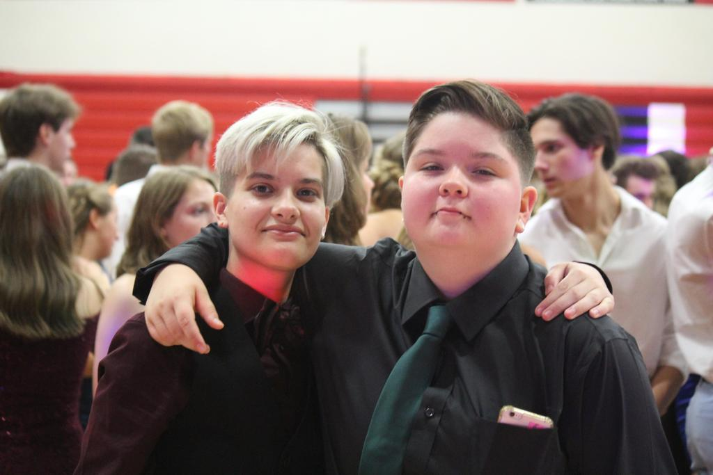 Two students at a dance with their arms around each others' shoulders