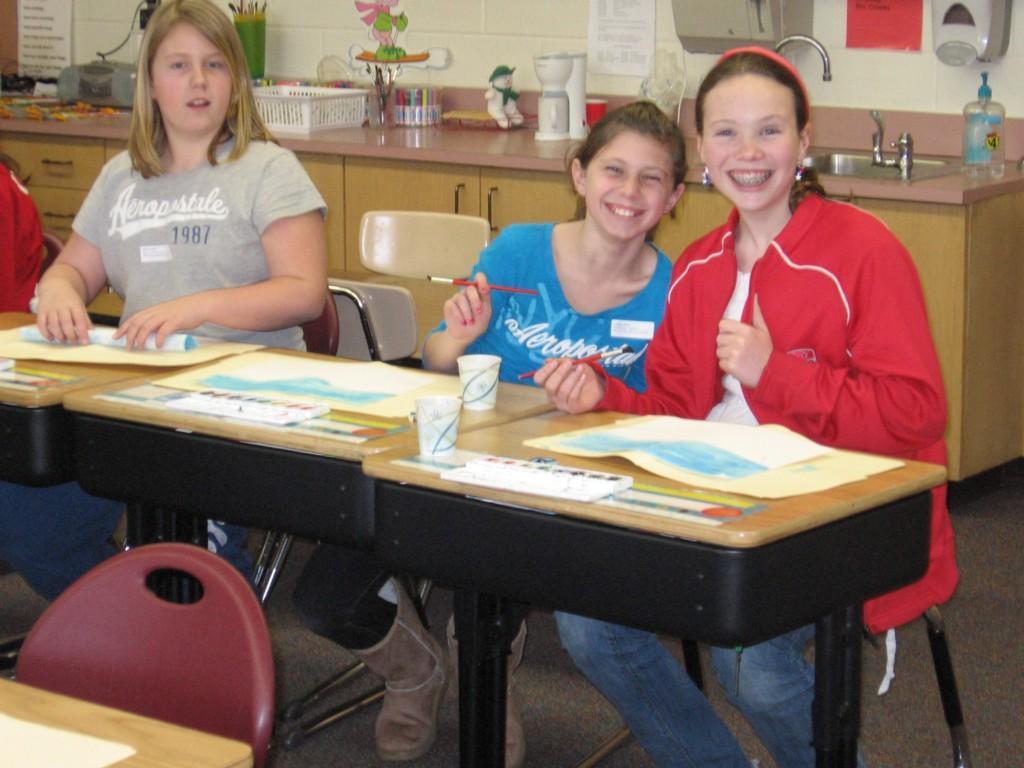 students paint at desks