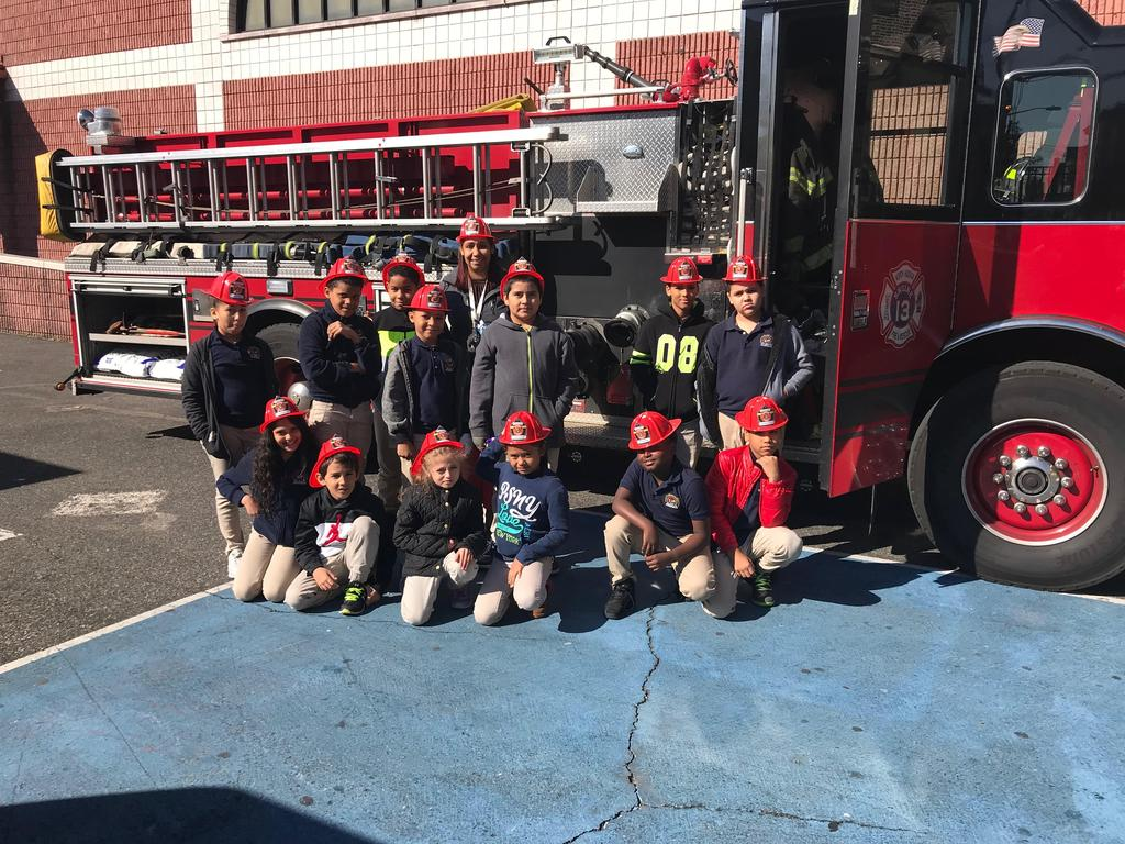 kids wearing their read fire hats in front of the fire engine