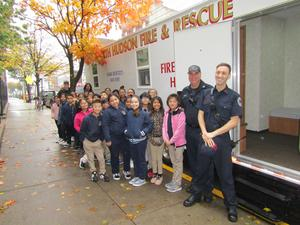 class in front of the mobile fire house with two fire fighters