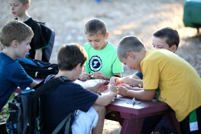 group of kids coloring outside on table