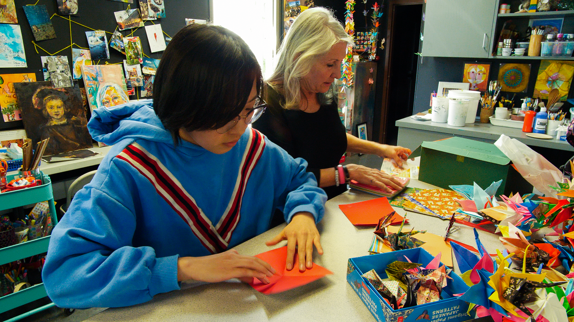 Ms. Rudolph works with art club on an origami crane project.