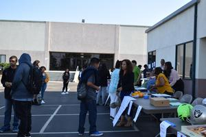 Teachers talking to students and giving them donuts.