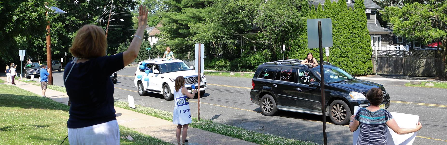 Photo of Franklin principal and staff waving to 5th graders during Grade 5 Clap Out Car Parade.