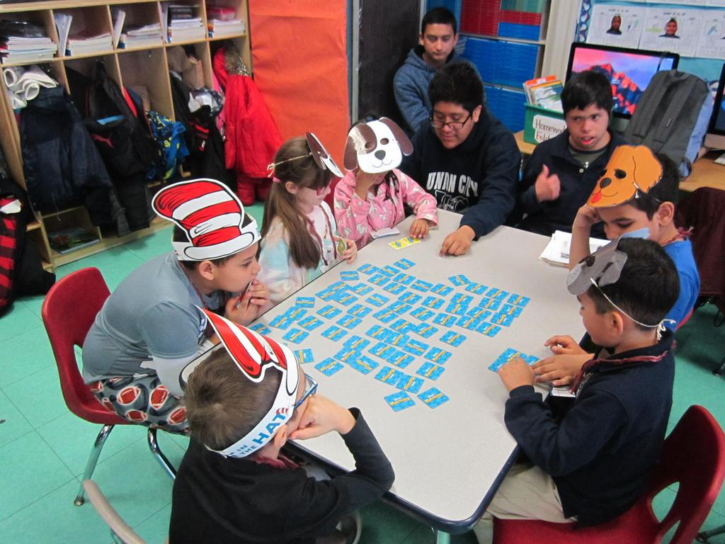 UCHS male student playing a dr. seuss game with the group of children