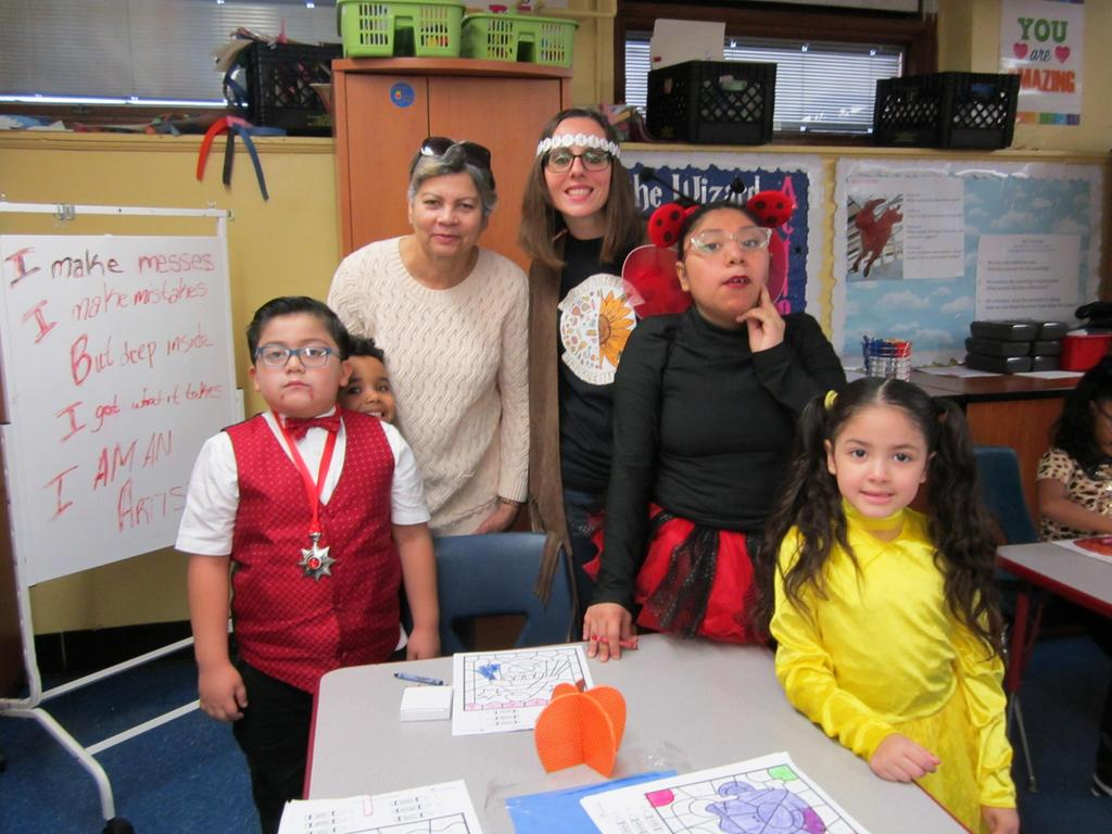 Ms. Viera, aide, female student dressed as lady bug with two students coloring at a table