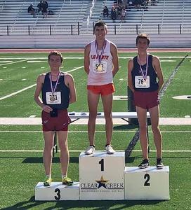 Three distance runners standing on winners' podium