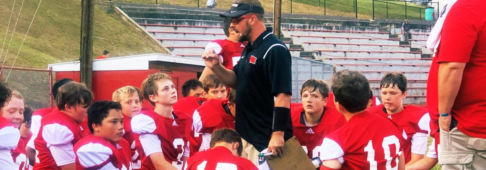 Coach Neese talking to football players during half time.