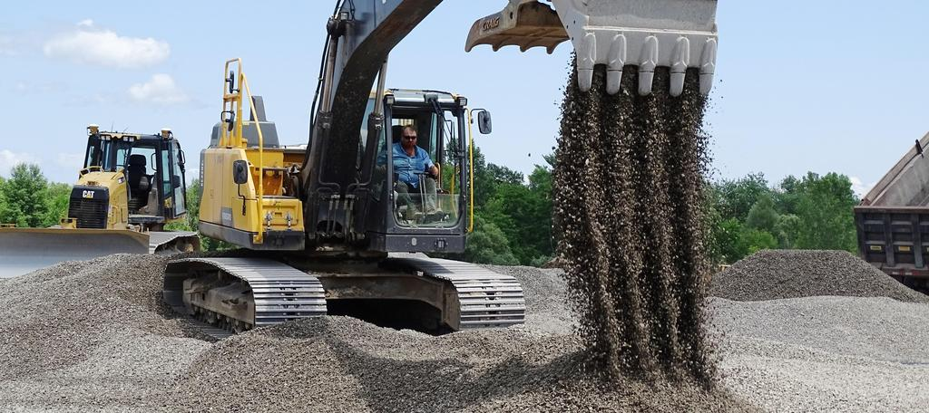 Site construction company J.E. Sheehan's crew is pictured Monday, July 15, 2019 in the process of delivering, distributing and leveling a layer of stone on the new feature field that has been under construction during recent months. An excavator operator is helping to distribute that stone on the field.