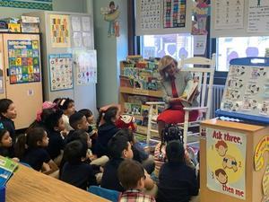 Comm. Grullon reading to students