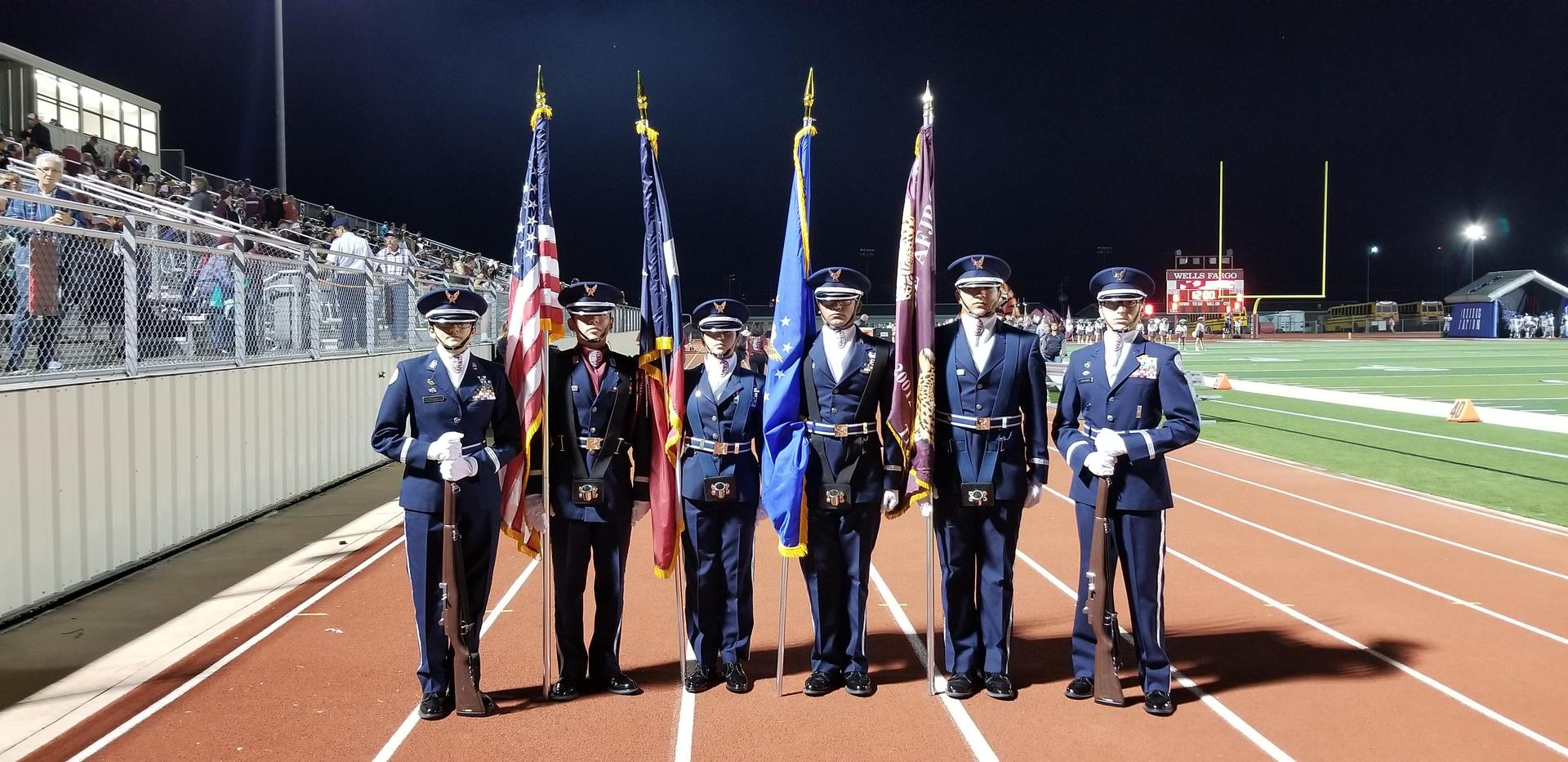 JROTC members posing with the colors at a Tiger Football game