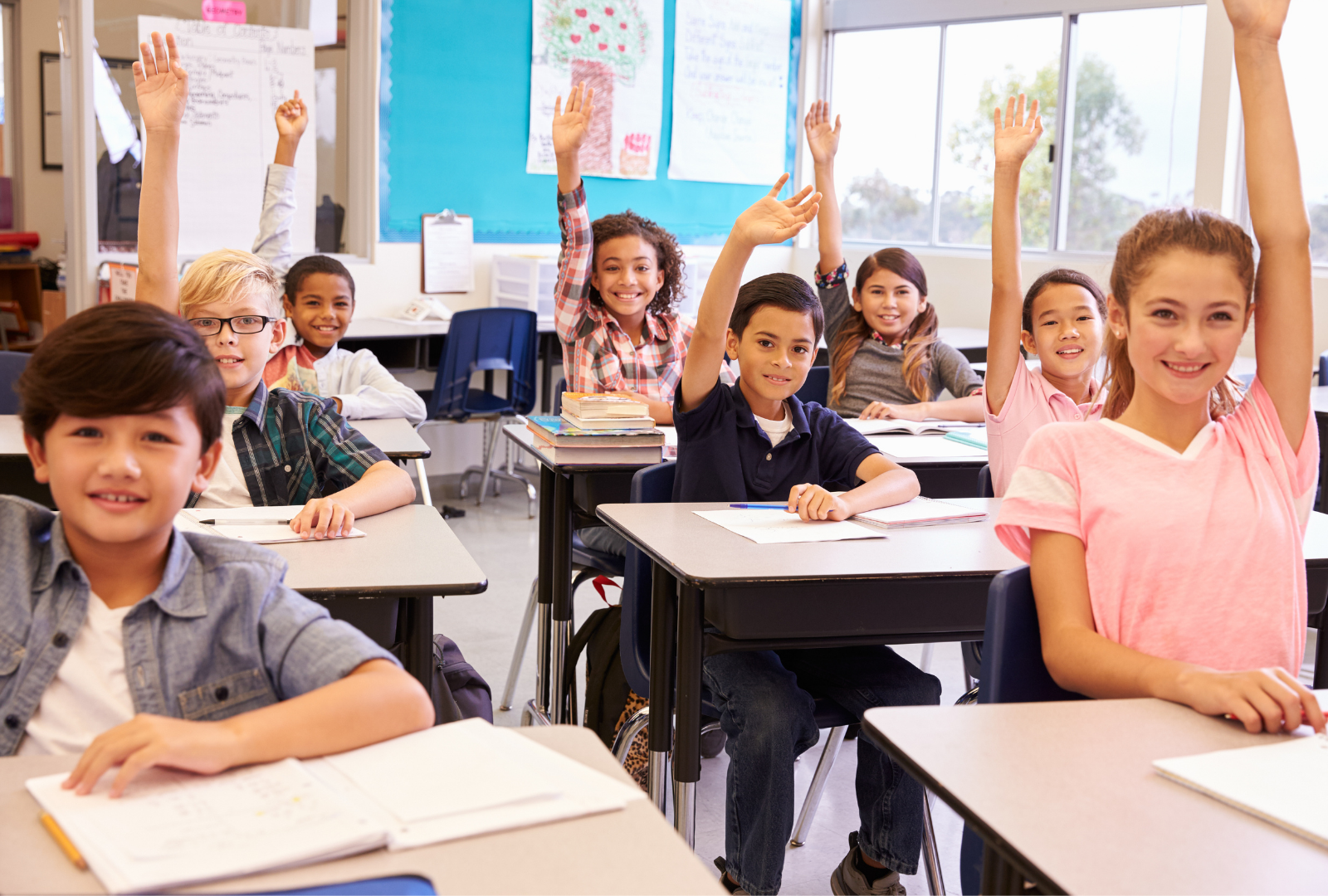middle school students raise their hands at their desks in the classroom, smiling