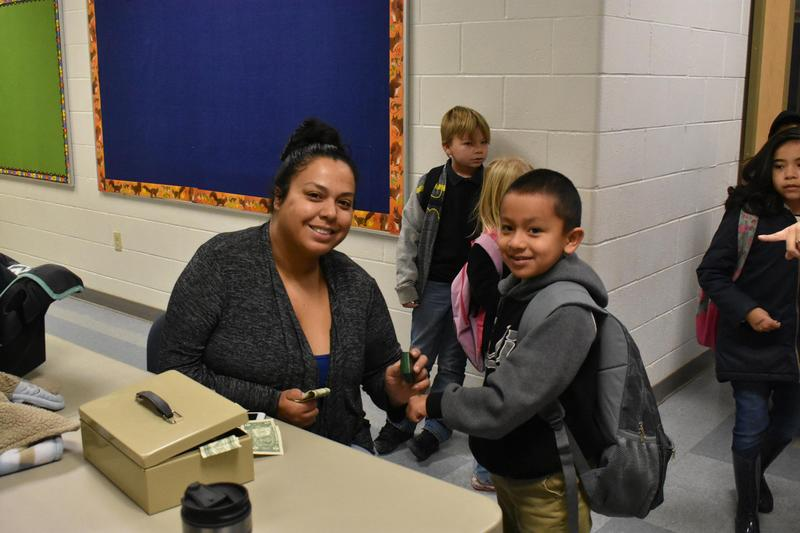 A student handing a dollar to our PTO president.
