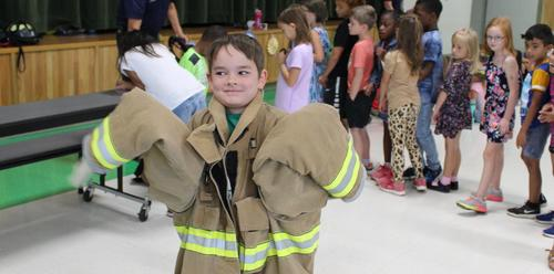 One of our students trying on a fireman's coat for Fire Safety