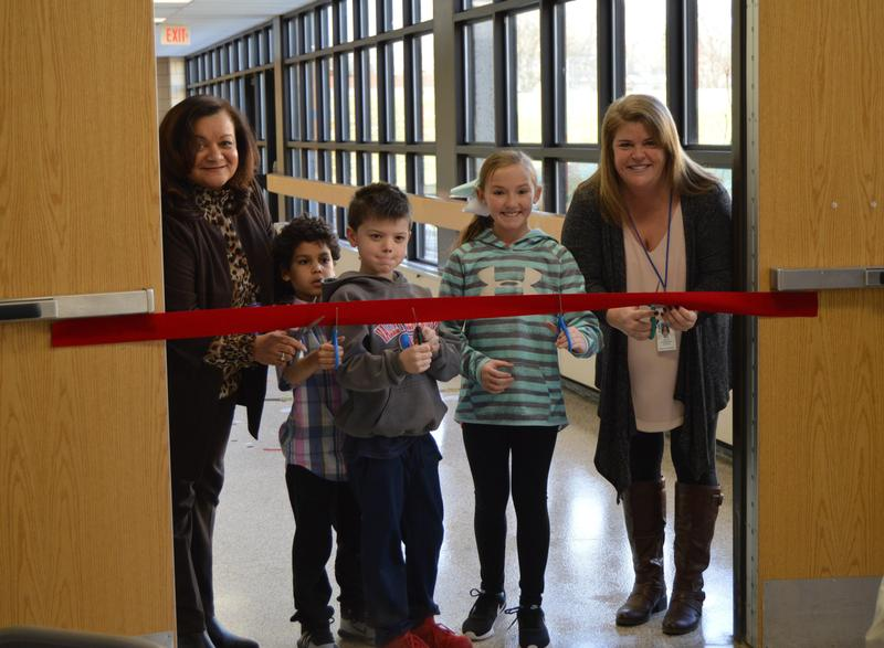 Valley principal Mrs. Toller and 2 boys and a girl along with Special Education teacher Ms. Hill have scissors on a red ribbon prior to cutting it.