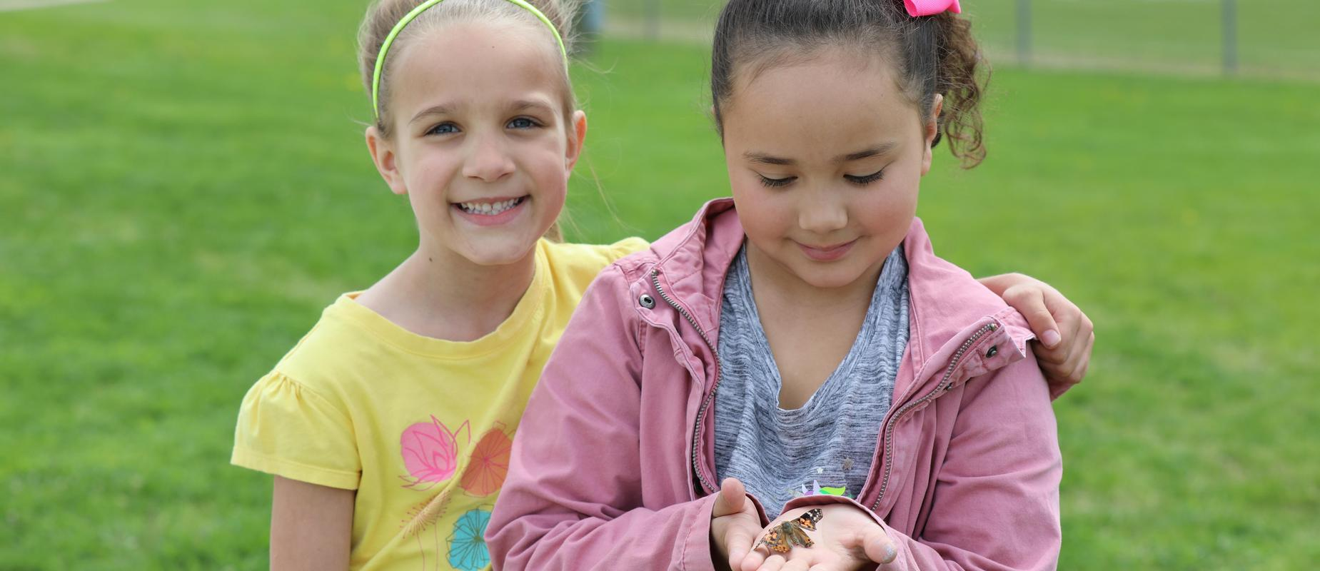 2 girls with butterfly outside in their hands