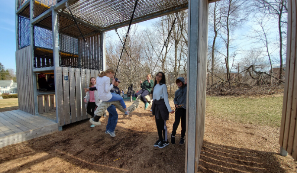 Students swing in the Dragon's Rock play area.