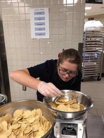 Adult Student wearing gloves is filling a bowl with chips in a school cafeteria