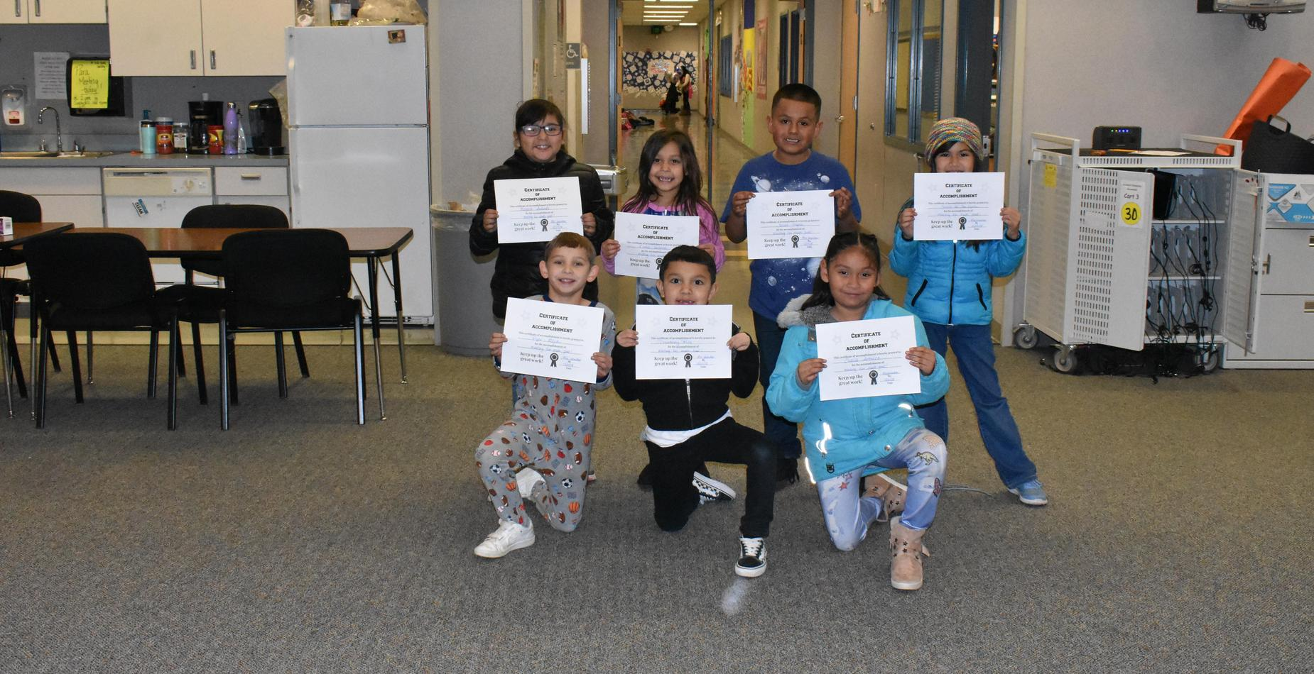 Seven students holding certificates for meeting their math goals!