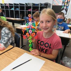 A student makes a colorful flower using Brain Flakes.