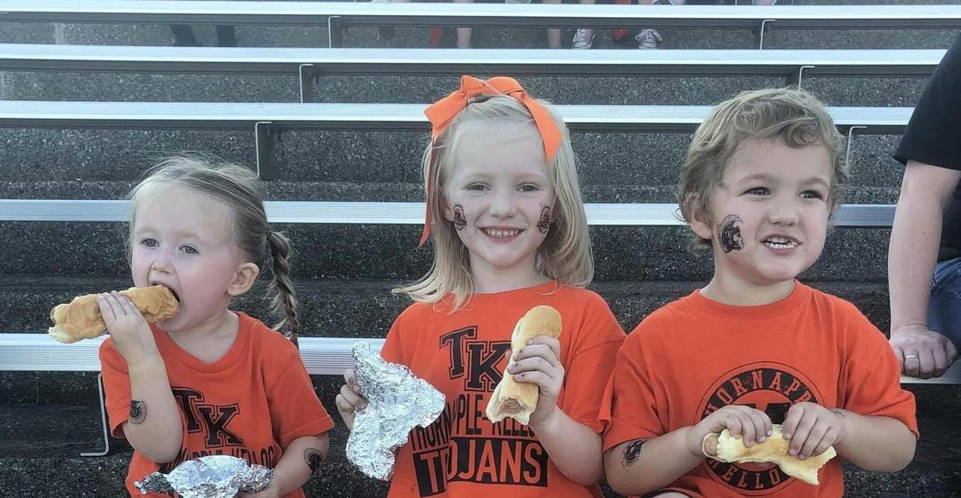 Youngsters enjoy free hot dogs at the homecoming game.