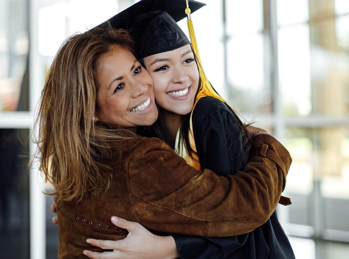 A mother hugging her daughter at a graduation ceremony