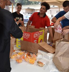 PC football players packing a meal for the opposing team to eat on their way home from a PC home game