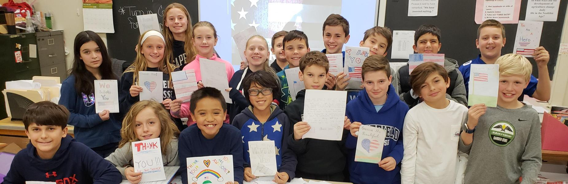 Students at Roosevelt Intermediate School hold cards/letters they wrote to be sent to troops serving overseas.