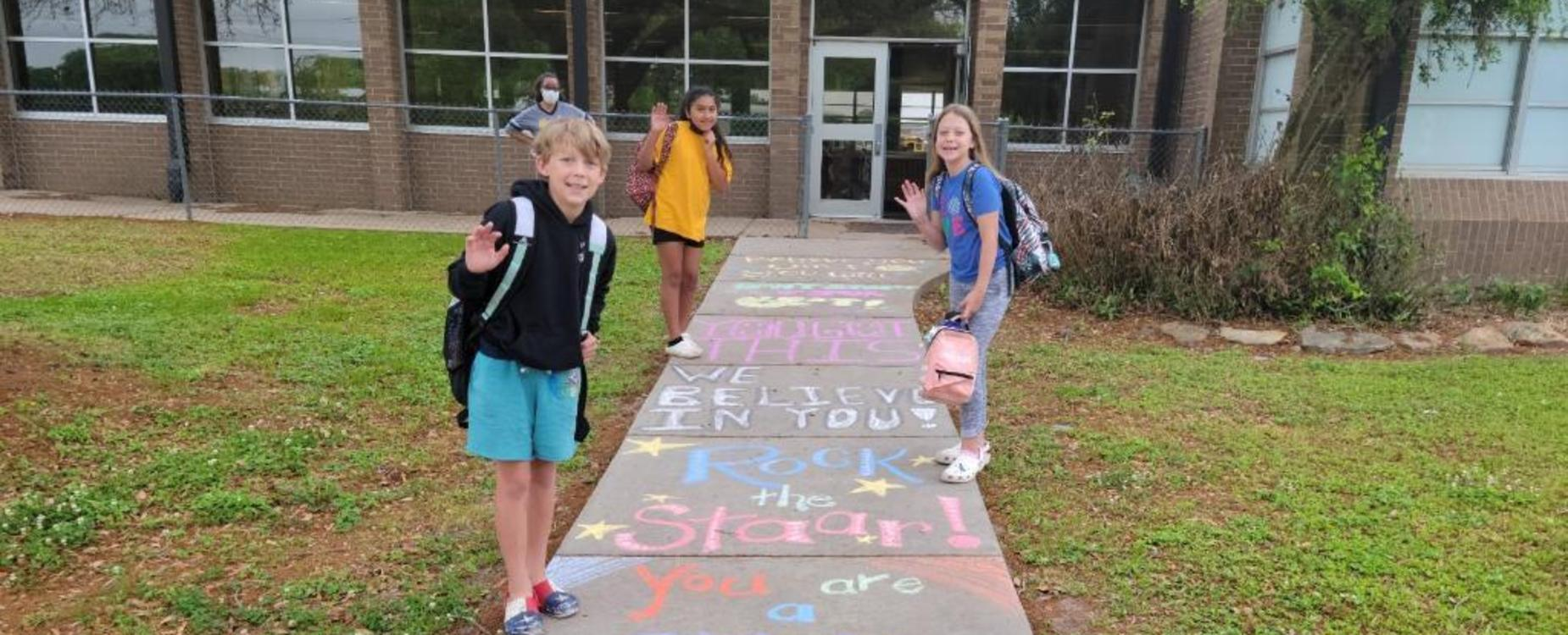 students on a chalk decorated sidewalk