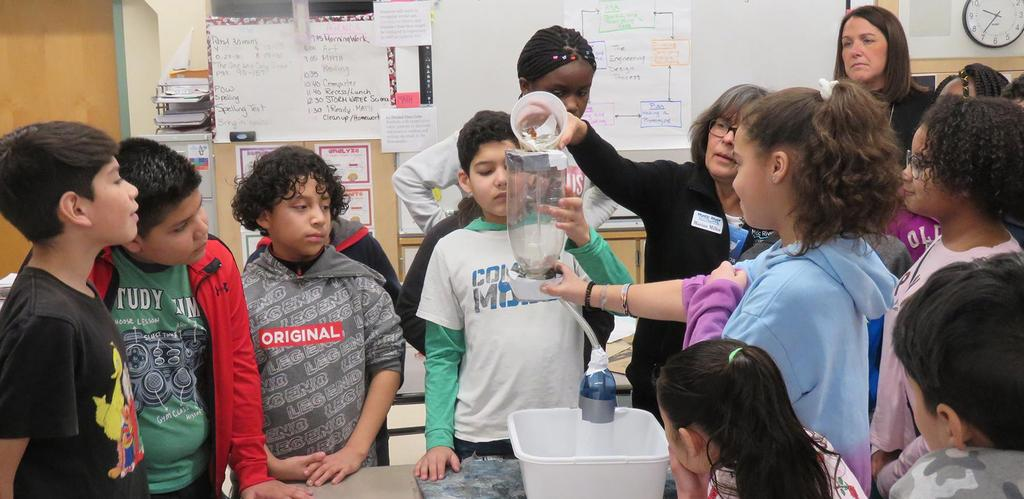 Keverian fifth graders gather around a table to test a filtration device