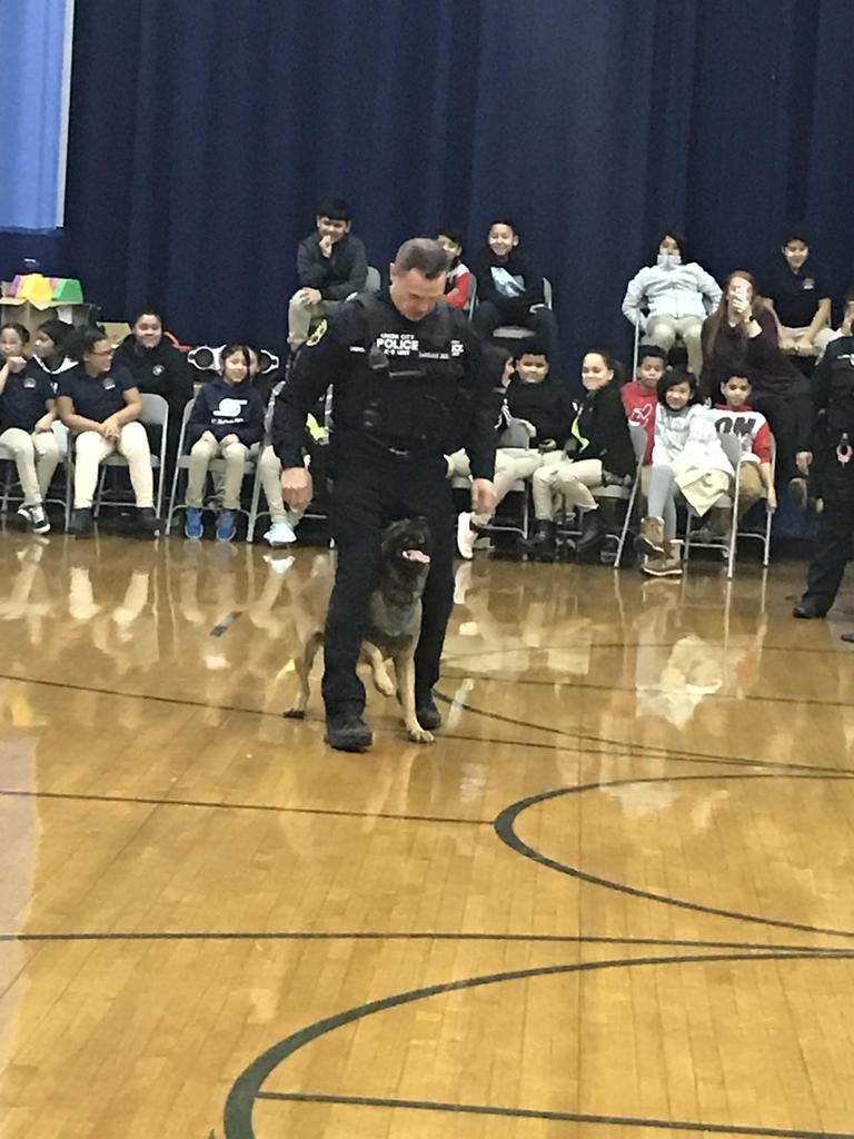 police doge between the police officers legs in the gym infront of the children sitting down in gym