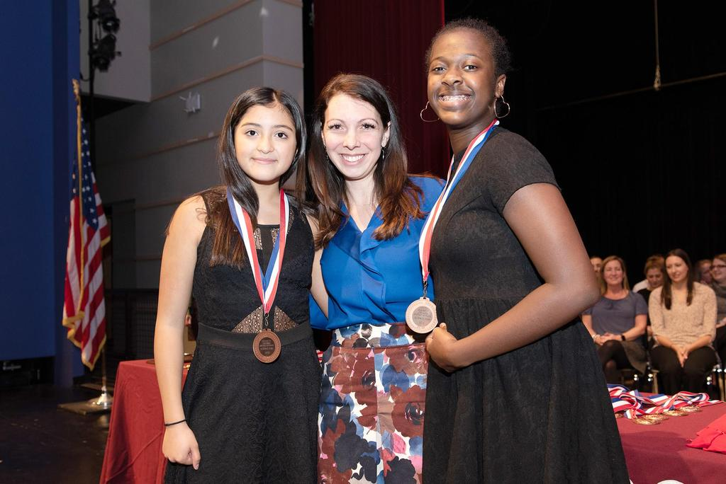 Teacher Katelyn Crossley presents medals to two sixth graders