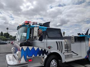 Maria Reyes at the wheel of shark-themed fire engine